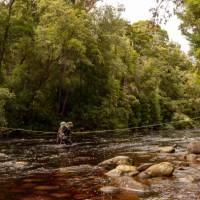Crossing a river on the South Coast Track in Tasmania | John Dalton