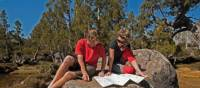 Enjoying the sunshine, reading maps on a Tasmanian Expeditions trek | Don Fuchs