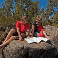 Enjoying the sunshine, reading maps on a Tasmanian Expeditions trek   Don Fuchs